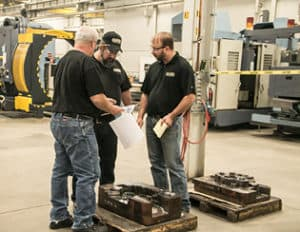 Men inspecting a product